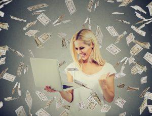 Successful woman using laptop building online business making money dollar bills cash falling down. Beginner IT entrepreneur success economy concept