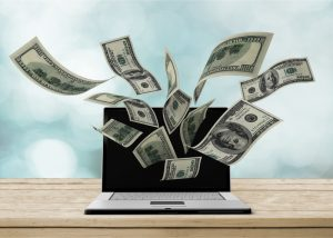 Laptop making money concept on background