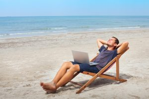freelancer with laptop on beach
