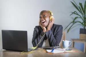 young happy black afro american woman listening to music with headphones excited and joyful working at laptop computer desk at modern workplace