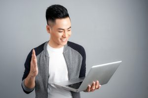 Excited happy asian man looking at laptop computer screen and celebrating the win isolated over gray background