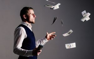 Richness and wealth concept. entrepreneur on arrogant face wasting money.