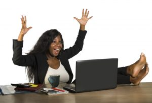 happy and attractive black afro American businesswoman working excited with feet on computer desk smiling relaxed celebrating business financial success
