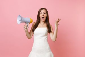 Portrait of excited bride woman with opened mouth in wedding dress holding megaphone, spreading hands isolated on pink pastel background. Organization of wedding concept. Copy space for advertisement.