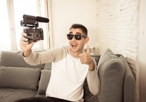 Young happy blogger recording video on camera for internet blog showing thumb up
