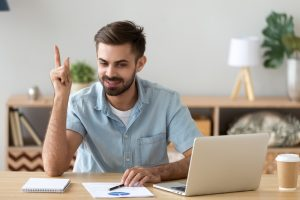 Satisfied man with raised hand thinking about good creative idea