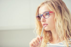 University student girl pensive with pen on her lips. Portrait of thinking woman with glasses.