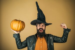 Excited happy man with pumpkin. Trick or treat. Thanksgiving seasonal cooking ingredients. Bearded man cook in Halloween hat with pumpkin.