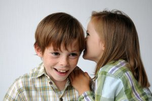 children telling secrets