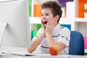 Surprised boy with computer