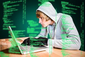 Focused man with hoodie typing on laptop against green background with vignette