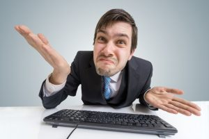 Confused frustrated and unsure man is working with computer.